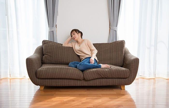 疲れてソファで休む女性